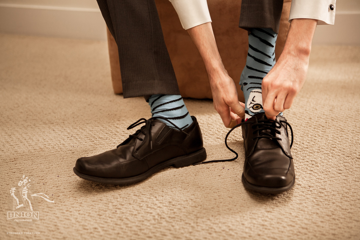 groom putting on his shoes with his funky socks