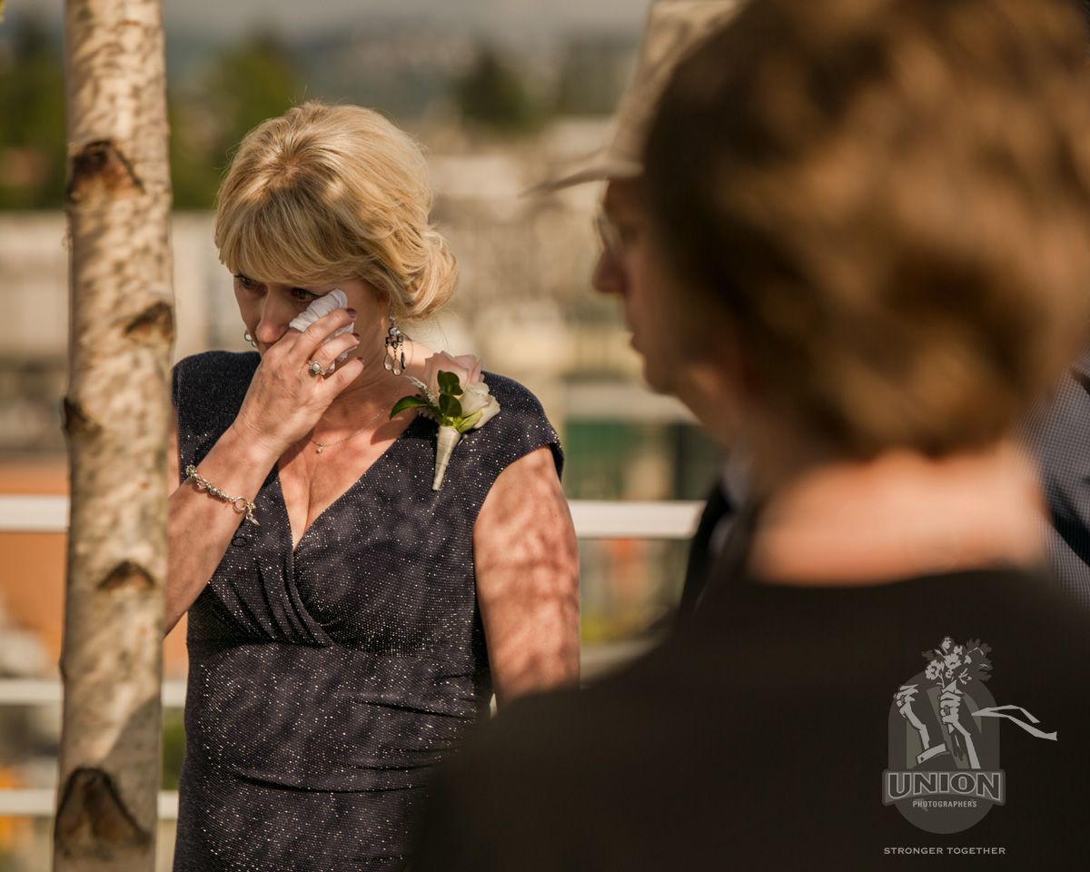 mother of the groom wiping tears from her eyes
