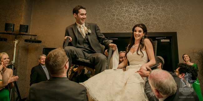 raising the newlyweds up in chairs