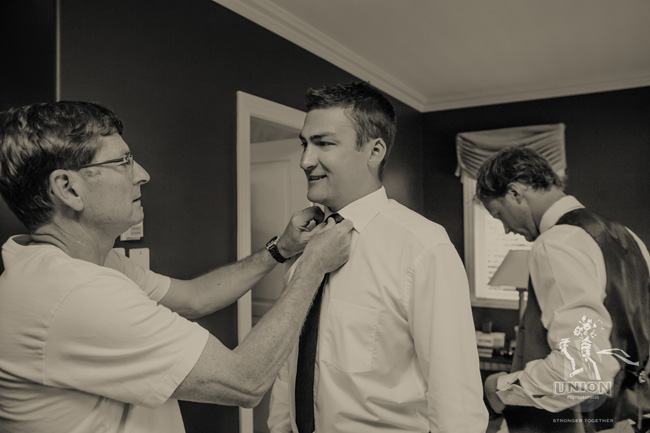 Dad helping the groom with his tie