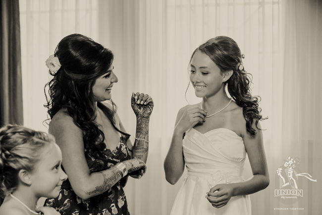 bride giving necklaces to her flower girls